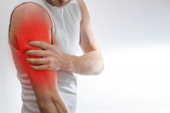 A man in a white T-shirt holds on to the shoulder, arm, wrist,. Forearm, sports injury, experiencing pain, on a white background royalty free stock image