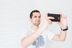 Man in white T-shirt take a photo on a white background Stock Photography
