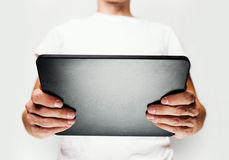 Man in white t-shirt using tablet pc Stock Photos
