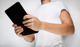Man in white t-shirt using tablet pc Stock Photo