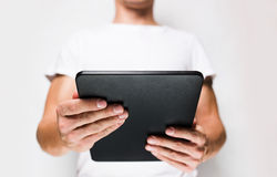 Man in white t-shirt using tablet pc Stock Images