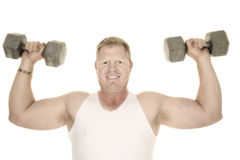 Man in white tank top flex with two weights. A man working out his shoulders with weights Stock Image