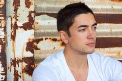 Man In White Tee Shirt. A male in his mid 20's sits in a boxcar that is old and decaying in a white t-shirt with nothing on it Royalty Free Stock Photos