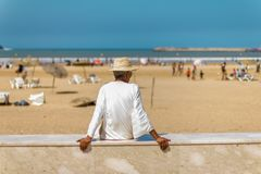 Old man in a white tunic and a straw hat sitting on the beach stock images