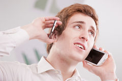 Man in white with two mobile phones. Man in white holding two cell or mobile phones to his ears, multitasking, calling or listening Royalty Free Stock Image