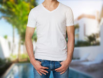 Man in a white V shape t-shirt, hands in pockets. Villa with swimming pool in blur on the background. Royalty Free Stock Photos