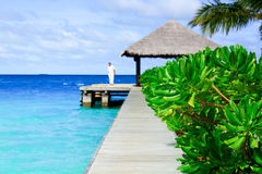 Man in white waits for boat on jetty royalty free stock photography