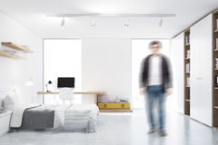 Man in a white walled bedroom with study corner Stock Images