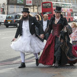 A man in a white wedding dress and a top hat with a woman in a gothic red velvet dress walking down the street in London Bridge Stock Images