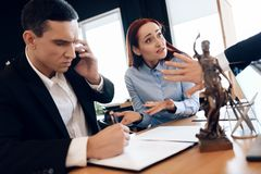 Man who divorces his wife consults on phone with lawyer. Disconcerted woman sits next to man talking on phone. stock photography