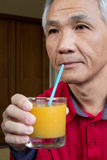Man who drinking Orange juice Stock Photography