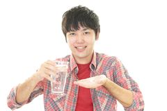 Man who drinks supplements. Isolated on white background stock image