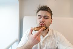 Man who eats a piece of pizza on a light background. A man in white gets pleasure from eating pizza. Royalty Free Stock Photo