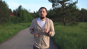 Man who is engaged in sports running is preparing for a sprint in the park area stock video