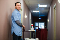 A man who is on the hotel cleaning crew staff is smiling with a towel vacuum in the process of cleaning the hotel rooms. A man who is on the hotel cleaning crew stock images