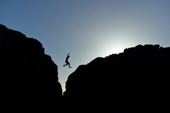 Man who jumped on the rocks in silhouette Royalty Free Stock Photos