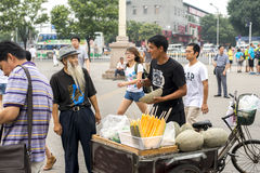 A man who sell hami melon with an old man in communication, in the streets of Beijing Royalty Free Stock Images