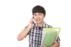 Asian man holding a smart phone. Man who is talking on a smart phone stock photo