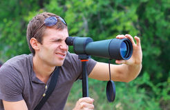 Man who is watching in spotting scope. Royalty Free Stock Image