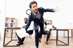 A man whose back is written kick me, someone is kicking. A men whose back is written kick me, someone is kicking. His business colleagues are joking at him on royalty free stock images