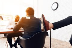 A man whose back is written kick me, someone is kicking. A men whose back is written kick me, someone is kicking. His business colleagues are joking at him on royalty free stock photo