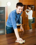 Man with wife dusting furniture Royalty Free Stock Photography