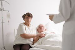Man with wife listening diagnosis. Elderly dying men lying in hospital with caring wife listening diagnosis royalty free stock photography