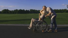 Man with wife in wheelchair enjoying outdoors stock video