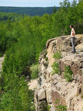Man in wilderness. Scenic view of bare chested man on cliff looking at picturesque forested landscape, Rocky Mountains, North America Royalty Free Stock Photography