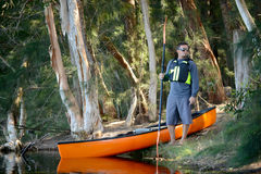 Man in the wilderness of a forest with a kayak Stock Image