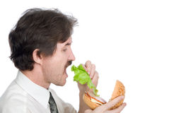 Man will get from hamburger sheet salad and eats Royalty Free Stock Photography