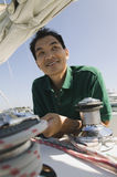 Man By Winch On Sailboat Royalty Free Stock Photography