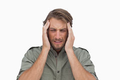 Man wincing with pain of headache. On white background Stock Photography