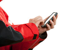 Man in wind jacket using mobile phone sending sms. Closeup of male hands using mobile phone. Young man sailor wearing red waterproof wind jacket sending sms Royalty Free Stock Photo