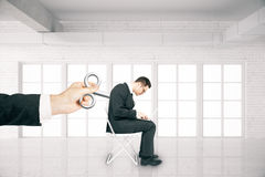 Man with wind-up key. Hand activating businessman with a wind-up key on his back in white brick room. Concept of control Royalty Free Stock Photography