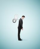 Man with winder. Businessman stands without energy with the winder back Stock Photo