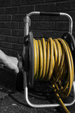 Man winding a hose pipe reel Royalty Free Stock Images