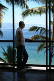 Man by the window. Man standing by the window in a tropical resort Stock Image