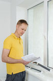 Man with window blind. Man is reading instruction for the installation of window blind stock photography