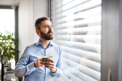 A man by the window holding a cup of coffee. Smart home. A man standing by the window, holding a cup of coffee. Smart home control system royalty free stock photos