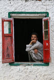 A man on  window. A Kashmir man looks through the window of his house in downtown Srinagar Stock Image