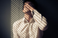 Man by window with shadows from blinds Royalty Free Stock Image