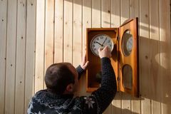 A man winds up a mechanical watch. The mechanical watch is hanging on the wood wall. The man winds the clock with a key Royalty Free Stock Photo
