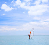 A man on a windsurf. A riding on a windsurf on blue sea stock image