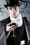 Man with a wine. Portrait of a young gentlemen wearing dinner jacket and black top hat. Shot in a studio Royalty Free Stock Photo