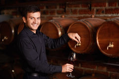 Man with wine. Sommelier pours wine from a barrel Royalty Free Stock Photos