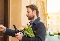 Man with wine and flower bouquet ringing doorbell Stock Photos