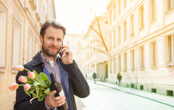 Man with wine and flower bouquet talking on a mobile phone - city Royalty Free Stock Images