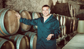 Man wine house technician working in storage. With wooden barrels Stock Photo