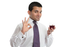 A man with wine shows approval or excellence Royalty Free Stock Images